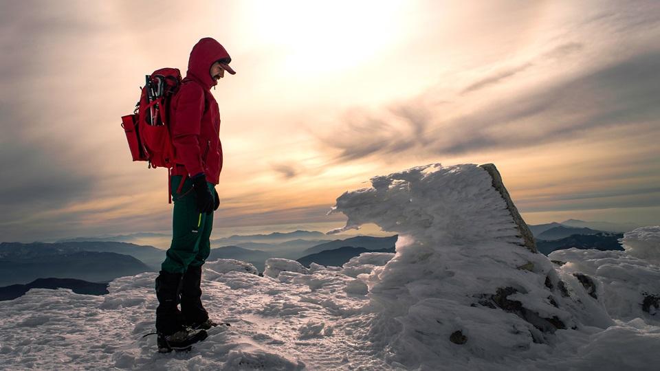 Mężczyzna zapatrzony na śnieg i lód w górach ubezpieczenia-lodz.com