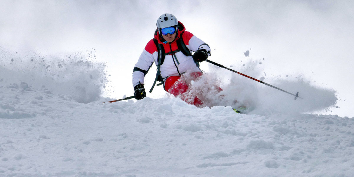 Mężczyzna jadący na nartach w śniegu ubezpieczenia-lodz.com