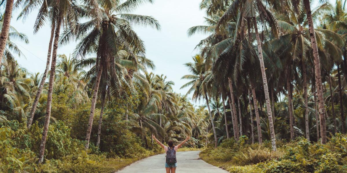 Kobieta idąca drogą obok dżungli ubezpieczenia-lodz.com
