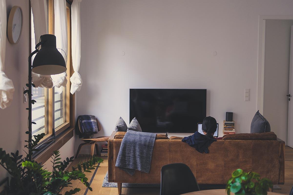 Kobieta używająca laptopa w salonie w mieszkaniu ubezpieczenia-lodz.com